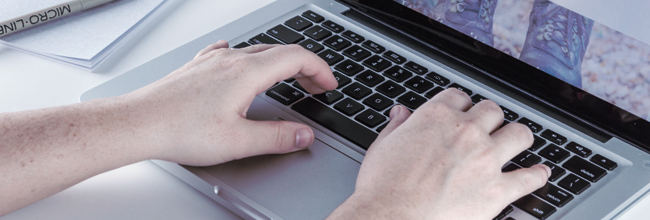 A close-cropped photo of hands typing at a sleek laptop keyboard.
