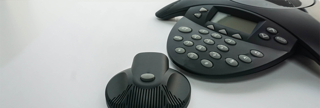 Close up of an IP conference phone with portable speaker sitting on a desk.